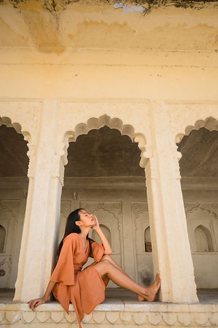 young beautiful woman posing with sand-stone color wrap around dress on ancient rajasthani building