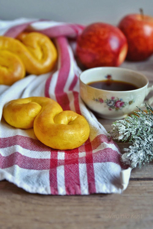 Lussebullar på en röd och vit kökshandduk med en fyllt kaffekopp vid sidan om. Röda äpplen bakom och granbarr framför.