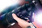 Hand hält eine Kamera