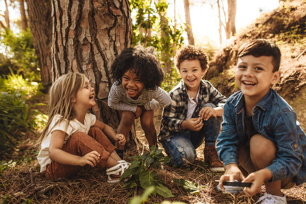 Group of cute kids sitting together in forest and looking at camera. Cute children playing