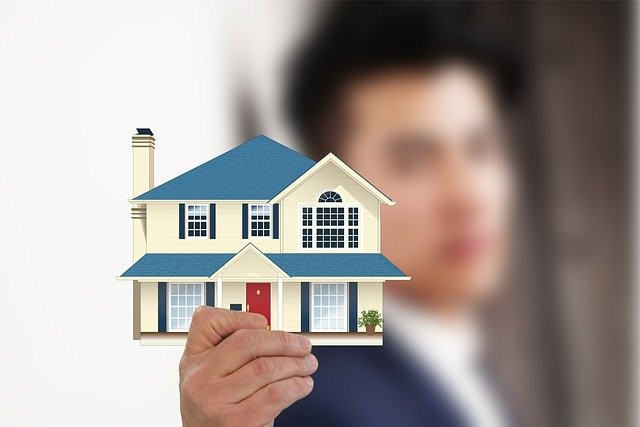 Man holding an image of a house