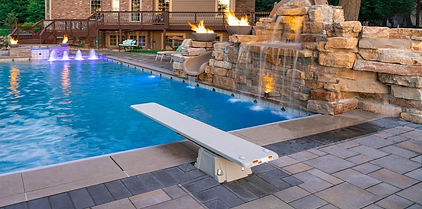 inground pool with diving board and rock wall slide
