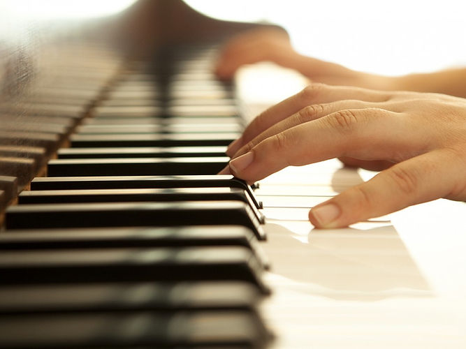 Hands-over-piano-in-warm-tones-28931582.jpg