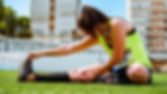 woman-sitting-and-stretching-on-grass-fi