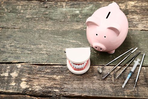 Pink piggy bank with teeth model and med