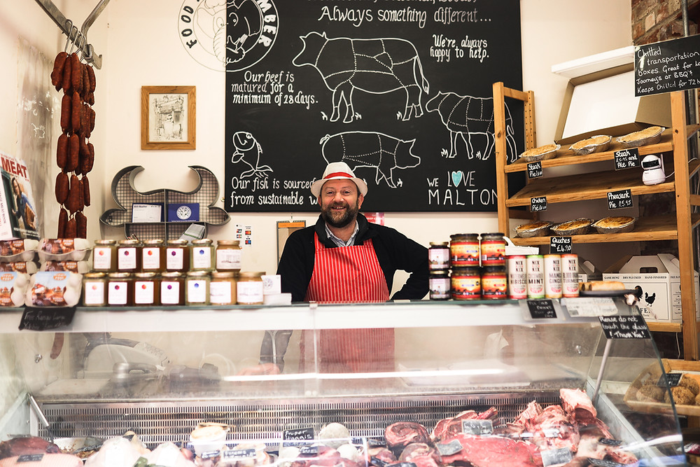 Butcher behind his counter
