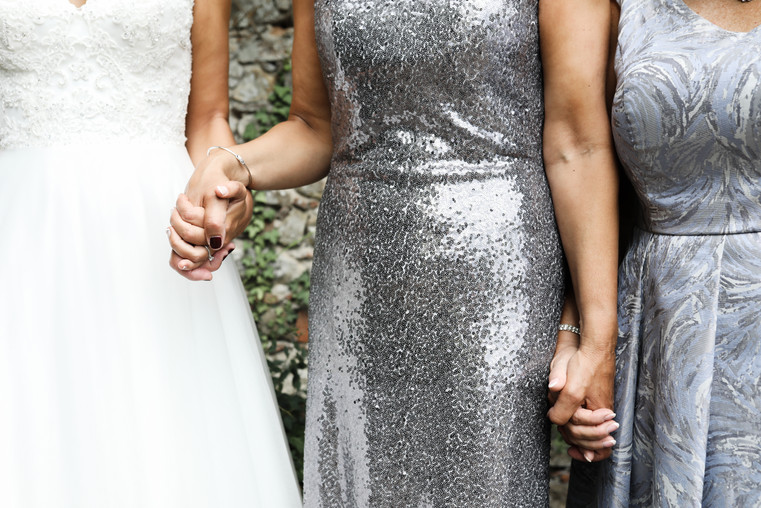 Detail shot of guests holding hands