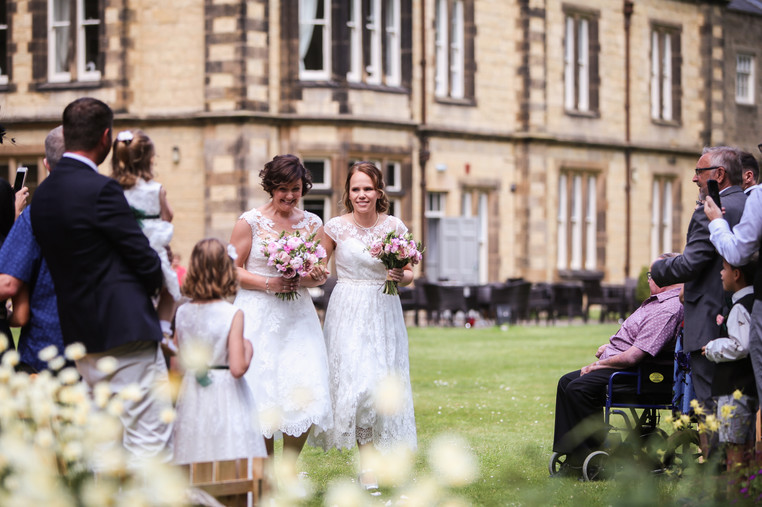 Mrs and Mrs to be walking down the ailse together at The Old Lodge, Malton