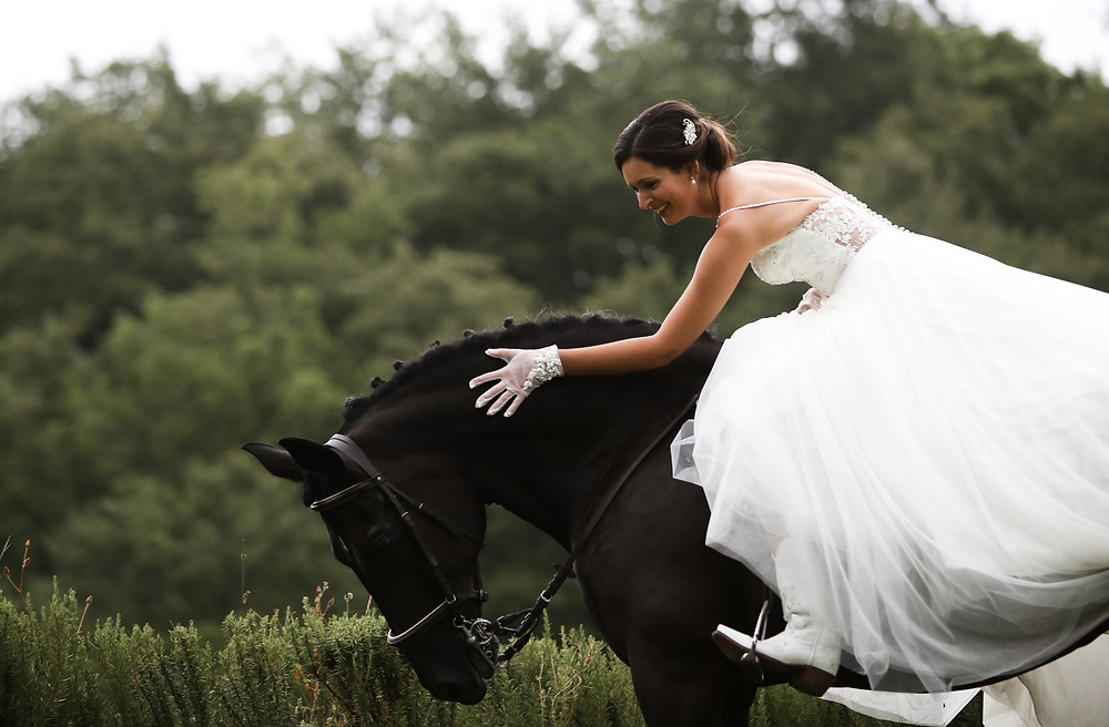 Natalie riding a beautiful black horse, in her wedding dress.