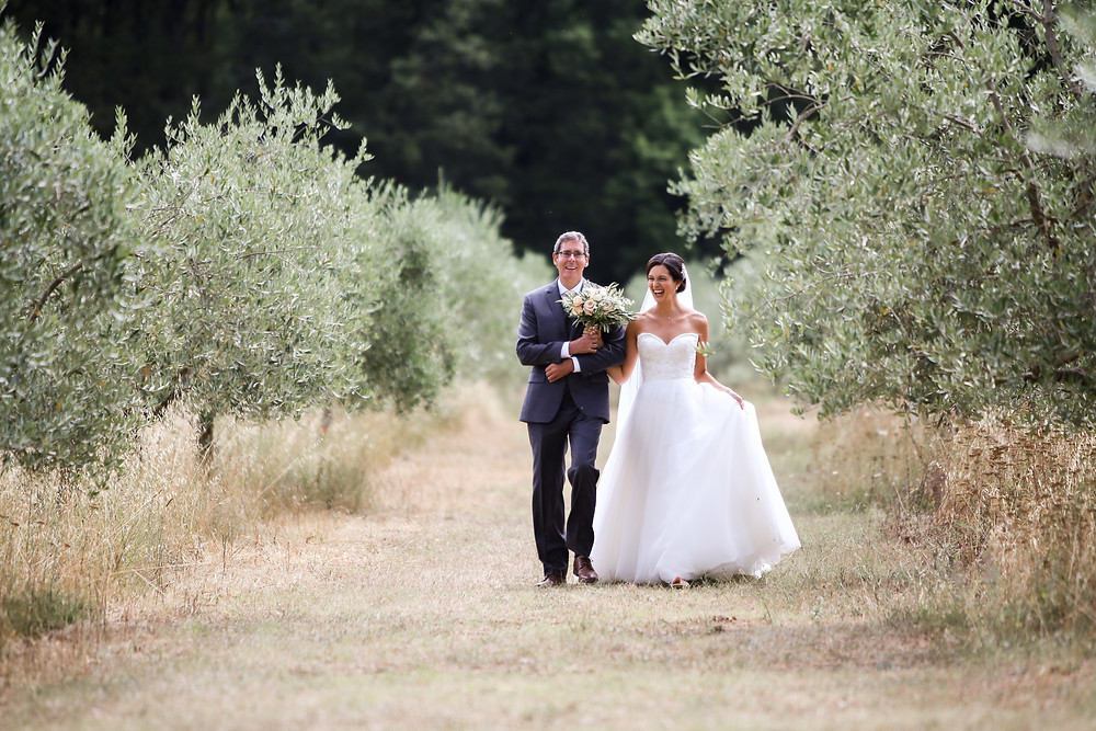 Dad walking Natalie down the aisle of Olive trees, in Italy