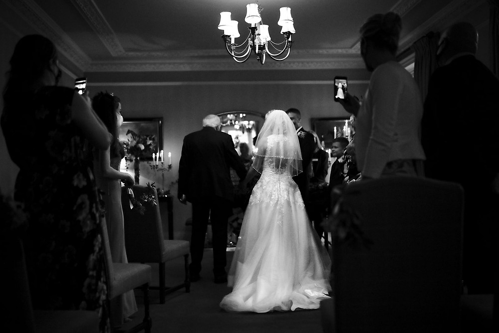 Walking her down the aisle to her groom.
