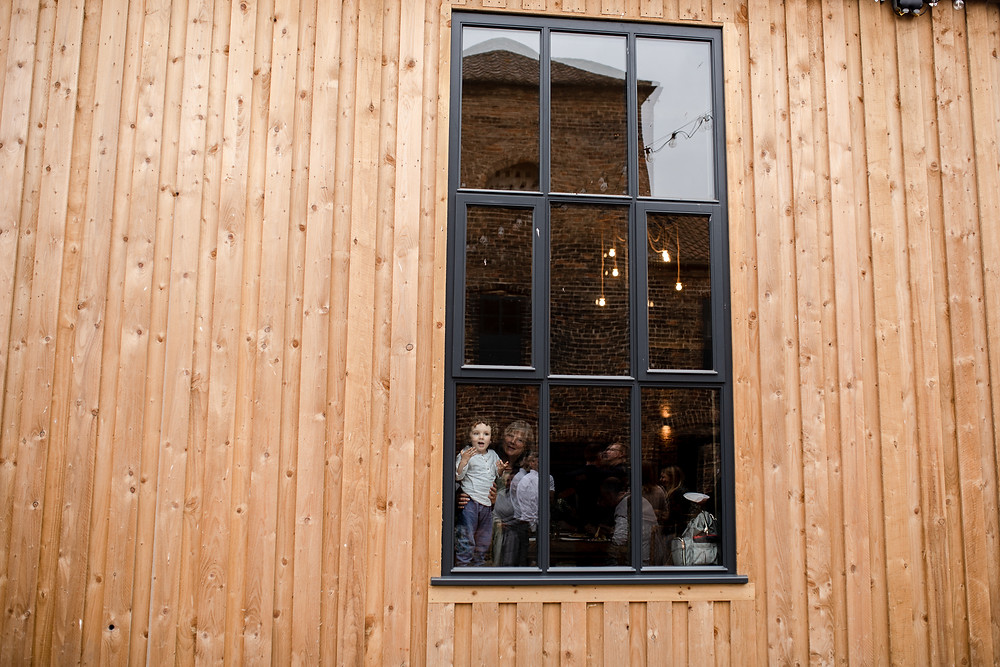 Little boy looking out of window at Lodge Farm, Wedding venue