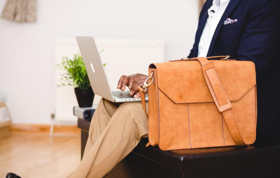 man seated with laptop and briefcase