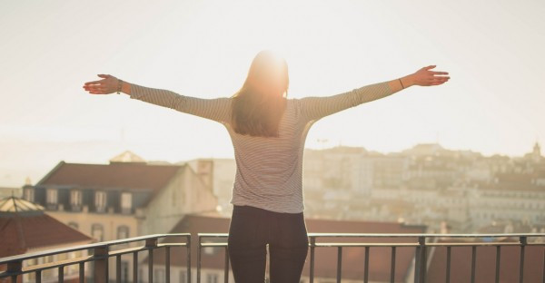 woman with outstretched arms in front of city