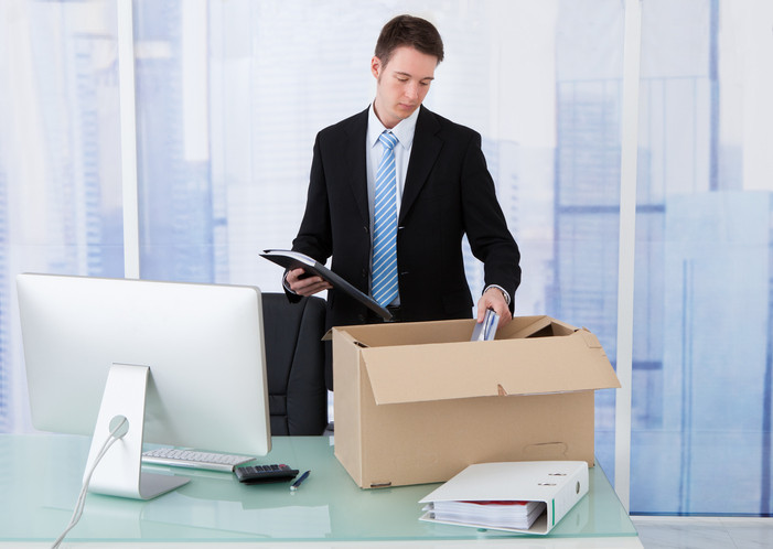 man in business suit packing up office materials