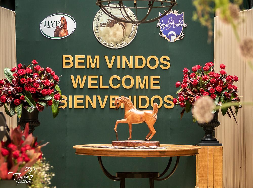 Hall de entrada da Arena HVP Arabian & Royal Arabians com frase de bem-vindos em inglês e espanhol, vasos de flor, quadros com logotipos e escultura de cavalo árabe em madeira.