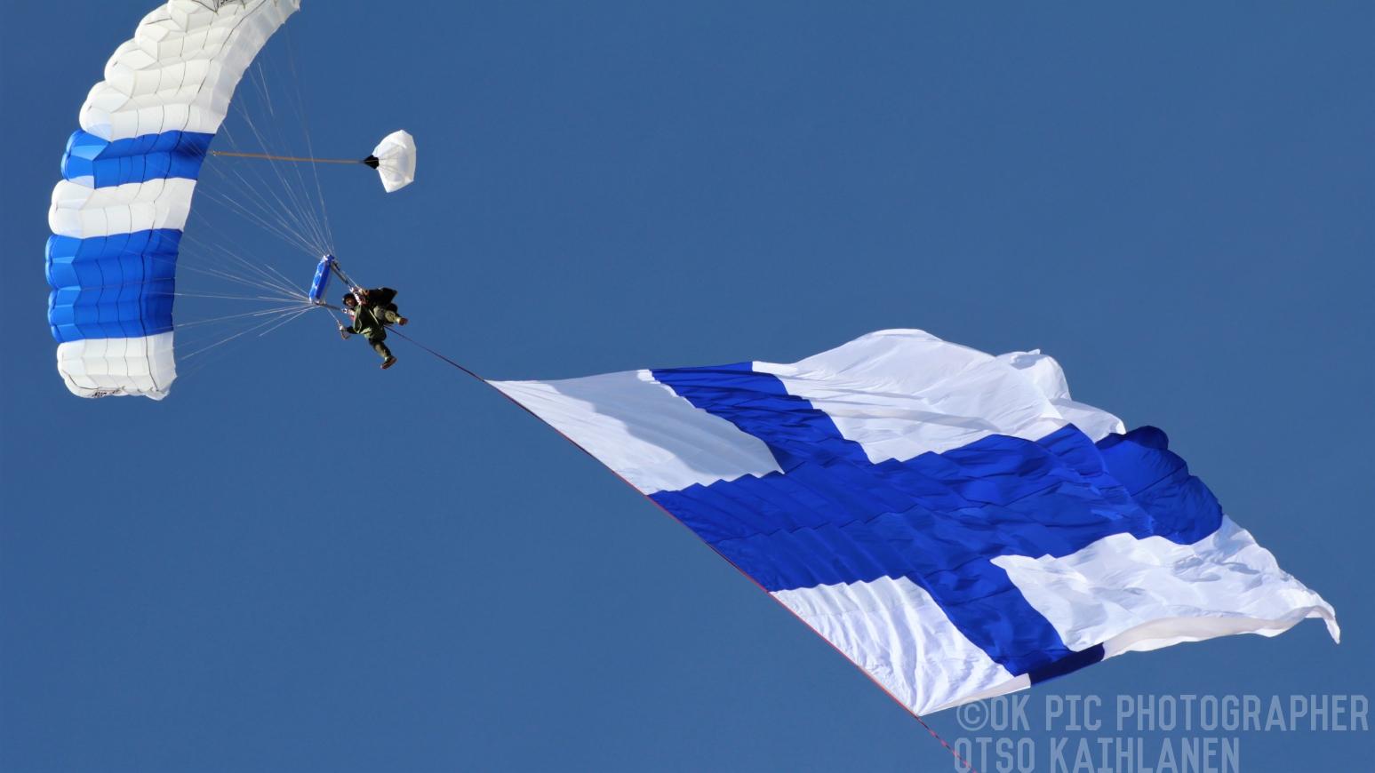 Laskuvarjohyppääjä Suomen lipun kanssa