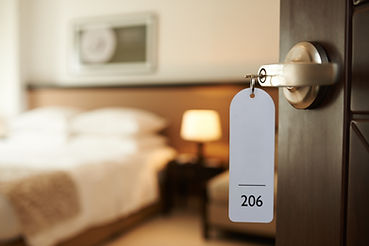 Opened door of hotel room with key in th