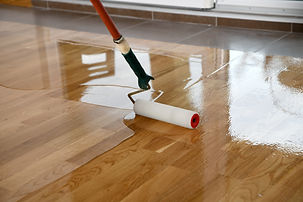 Lacquering wood floors. Worker uses a roller to coating floors. Varnishing lacquering parq