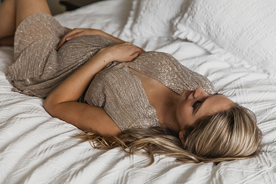Pregancy Photo in the home, women lying on master bed for photoshoot