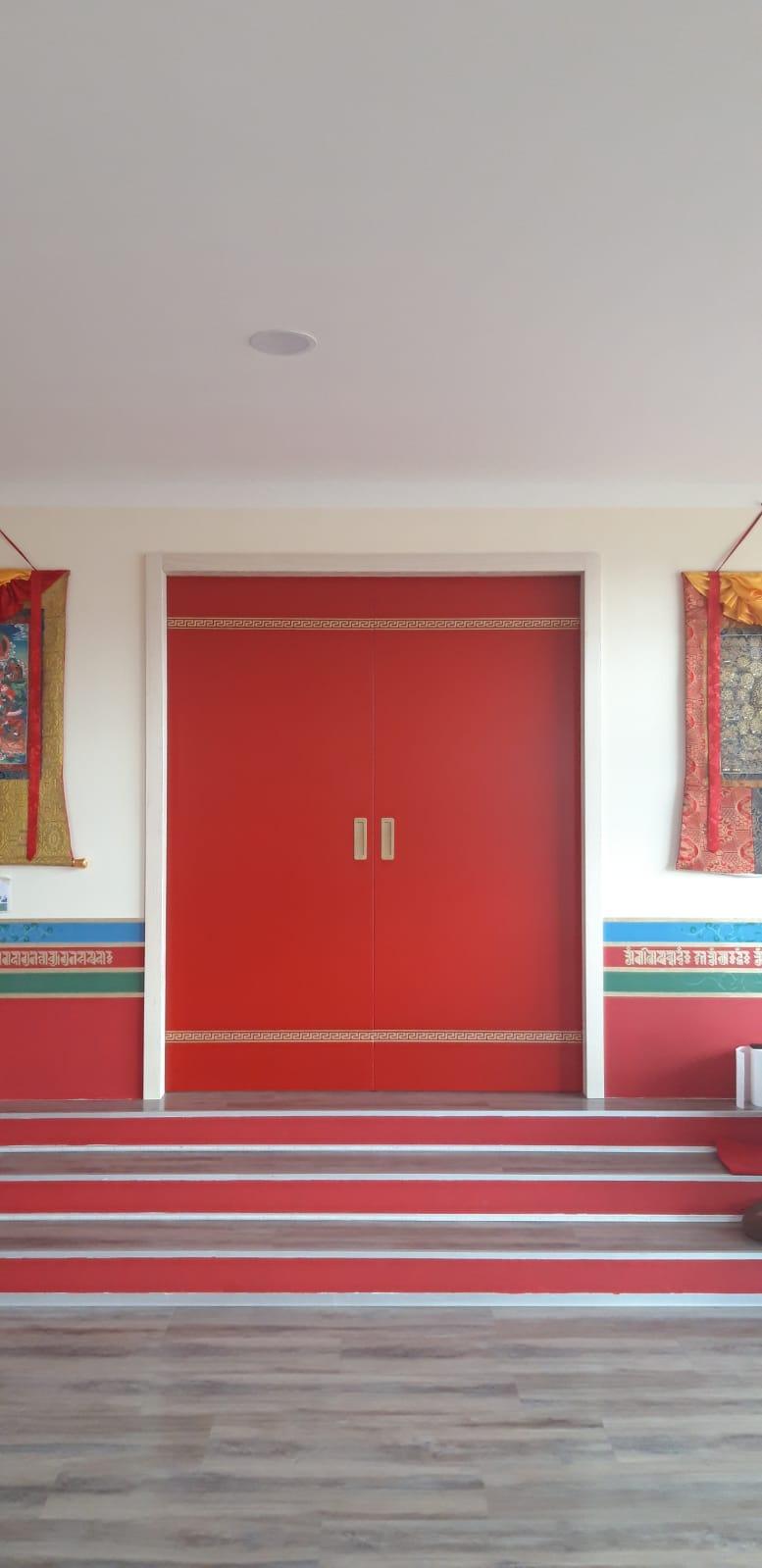 Dveře v gopmě s tradičními thangkami po stranách