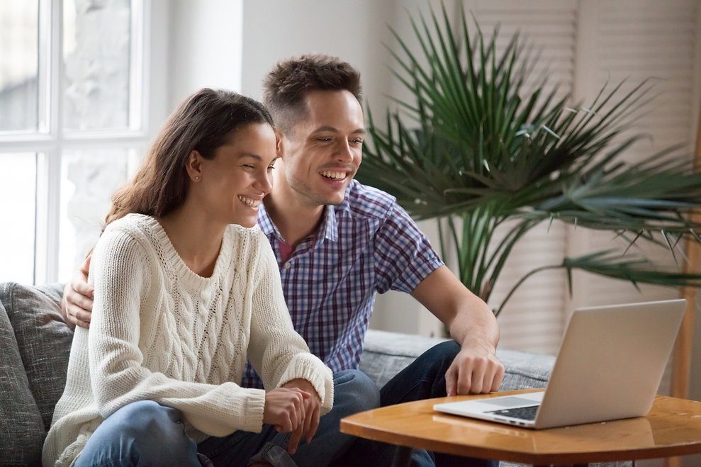 Happy-Young-Couple-Smiling-at-Laptop.jpg