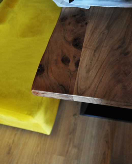 Wood table and mustard velvet sofa details.