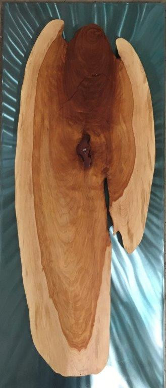 """Greg Lujan """"The Book of Tobit"""" 48"""" x 20"""" x 2"""" juniper wood, steel, proprietary colored wood filler, epoxy resin $2000.00  Depiction of the Archangel Raphael, who healed Tobit's blindness with the gallbladder of a fish. He also used innards of the same fish to cast away a demon, allowing a young couple to be married. Depicted here with a fish in his core. I found it within a slab of juniper wood left over  from the Stations of the Cross at St Joseph's on the Rio Grande church. It was gifted to me by the great New Mexico wood carver (my uncle) Joseph T. Sanchez.   ARTIST STATEMENT I am a mixed media artist, working primarily in wood and steel. My interest as an artist is to create beauty within manufactured wood and to reveal and display that beauty. Sometimes, when I'm lucky, the beauty just reveals itself and waits for my interpretation. My aim is always to create a strong visual impression. The materials sometimes tell a story. When they want to, I let them. Normally, I just want to make something that's fun to look at.  Contact: (505) 288-9646"""