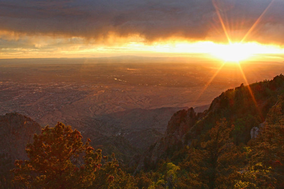 "Angela Holt ""Sunset at Storm's Pass, Sandia Crest"" 12"" x 18"" framed print photograph, 2020 $50.00  This year has forced many of us to slow down. It has given us the opportunity to explore and re- evaluate what is meaningful in our lives. For me, that has meant more time with my family and in nature. It has been a time for rest and restoration, to grow closer to each other and to God. This photo symbolizes the storm of our everyday busyness and distractions moving past and creating a space for the sun to set on skewed priorities and to rise on a day of hope and healing.  ARTIST STATEMENT Angela Holt works as the Director of Religious Formation at St. John XXIII Catholic Community. A wife and mother of two boys, she enjoys sharing her joy of reading and traveling with everyone she meets. She loves to stop and admire the beauty of nature - especially the sky - and can frequently be found snapping pictures of the breathtaking scenery around her.  Contact: (505) 463-6698"