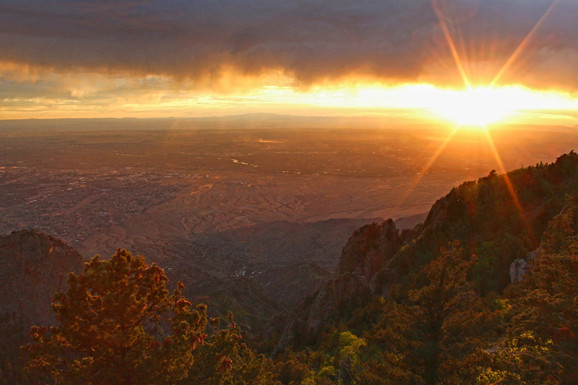 """Angela Holt """"Sunset at Storm's Pass, Sandia Crest"""" 12"""" x 18"""" framed print photograph, 2020 $50.00  This year has forced many of us to slow down. It has given us the opportunity to explore and re- evaluate what is meaningful in our lives. For me, that has meant more time with my family and in nature. It has been a time for rest and restoration, to grow closer to each other and to God. This photo symbolizes the storm of our everyday busyness and distractions moving past and creating a space for the sun to set on skewed priorities and to rise on a day of hope and healing.  ARTIST STATEMENT Angela Holt works as the Director of Religious Formation at St. John XXIII Catholic Community. A wife and mother of two boys, she enjoys sharing her joy of reading and traveling with everyone she meets. She loves to stop and admire the beauty of nature - especially the sky - and can frequently be found snapping pictures of the breathtaking scenery around her.  Contact: (505) 463-6698"""