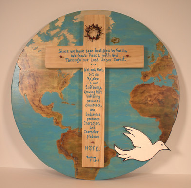 """Toby H. Herrera """"A Vision of Hope and Healing 2020"""" 11"""" x 17"""" x 3/4"""" hand-constructed wooden cross on wooden circular base  Assembled and painted with wood stain and oil paints. Other materials used include bailing wire, masonry nails, screws and glue. Throughout our earthly lives, on a worldwide basis, we face many trials and tribulations, sickness and pain, yet God is always with us. Through Him, our strength is renewed as he heals our wounds, physically, emotionally and spiritually. He meets our needs in sickness and in health; and tells us to not let our hearts be troubled, and to be not afraid. He is our Hope. During this trying 2020, we must hold true to the words found in Romans and rejoice in our sufferings which produce endurance that helps us to develop our character, which brings Hope forward.  ARTIST STATEMENT I am Toby H. Herrera, parishioner of Holy Rosary since 1959. My wife of 42 years is Bernice. We have three adult children, Maria, Lucia and Monique; and two grandchildren, Emma and Charlie. I am a retired educator of 42 years, now spending my time with family and in service to my church and community. Bernice and I are blessed to serve in many ministries, which we truly love. One of my interests is to dabble in art and crafts, which has led me to submitting a piece for this year's and each of the past Abbey Art Exhibitions."""