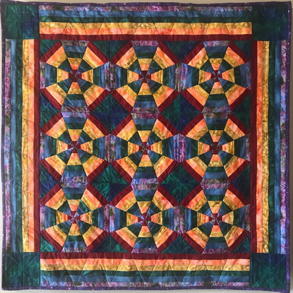 """Jennifer Murphy-Dye """"Reenvisioning Brokenness"""" 42"""" x 42"""" quilt, 100% cotton fabrics  I have named this quilt """"Reenvisioning Brokenness."""" In a departure from my usual appliqué art quilts, I used a pieced pattern, appropriately called """"kaleidoscope."""" A kaleidoscope is an apt symbol for these times; it uses broken pieces and shards and fashions them into something beautiful and whole yet different for each person looking through the lens. I selected vibrant colors in rainbow hues because biblically the rainbow represents the hope and the promise that we and our world will survive.   ARTIST STATEMENT Quilting is one of my passions, especially creating quilts with a positive message, incorporating the natural world, poetry, and theology. I love my faith, and currently teach Religion at Holy Ghost Catholic School as well as a course in St. Norbert College's MTS program. I am married to Brian, who graciously offers requested feedback on my designs, and have three children and two grandchildren. In my spare time of late, quilting has been pushed aside to allow for face mask sewing, which has become somewhat of an obsession – and a great way to use smaller pieces of fabric!"""