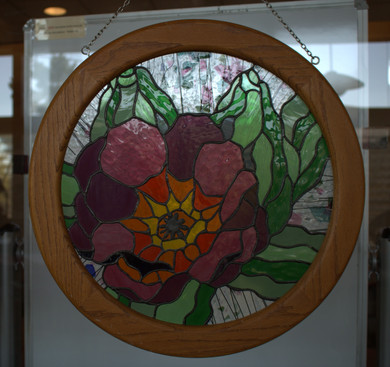 """Louise M. Nielsen, O. Praem.obl. """"The Desert Will Bloom (Isaiah 35:2)"""" Round approx. 19"""" diameter, handcrafted stained glass in a wooden frame  During this time of the covid-19 pandemic, fires and floods, and a country divided, there is hope for a brighter future. New life will spring from the ashes and we will once again be able to see more clearly the beauty of our world. When we have finished masking our faces, we will once again be able to share our smiles and shout our praises to the glory of God.  ARTIST STATEMENT Louise Nielsen is a Norbertine Community Oblate and a Pastoral Associate at Our Lady of the Most Holy Rosary. She loves to draw and design using natural subjects especially woodland animals and materials such as rocks and stones. Handcrafting small stained glass windows allows her to incorporate both the beauty of nature with the sacred light of glass. While time for artistic endeavors is limited, Louise finds that an artistic pause refreshes and lightens the spirit. Louise lives with her husband, six dogs, five birds, a fish, horse and cat and looks to nature for peace and delight."""