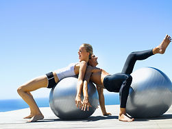 Fit young couple exercising on fitness b