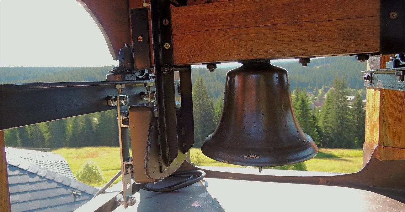 Bronzový zvon ve zvonici s elektrickým pohonem zvonění.