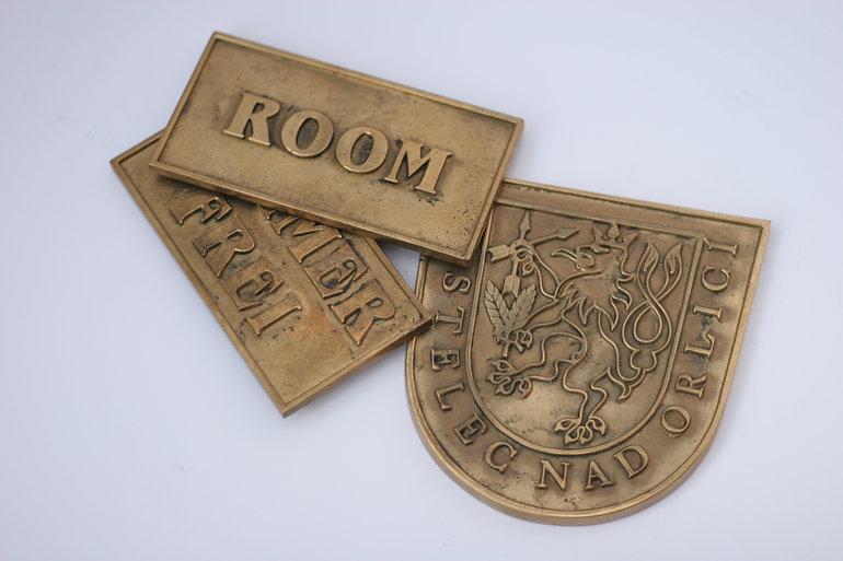 Reklamní a užitkové předměty lité z bronzu.