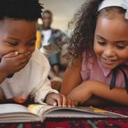 Front view of cute African American sibling lying on floor and reading a storybook in a co