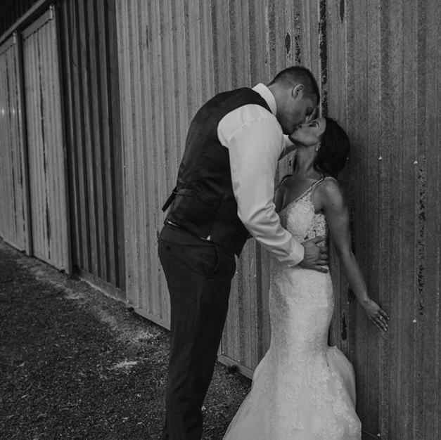A kiss for the new Mr and Mrs infront of the lodge