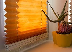 Pleated blinds with orange folded fabric