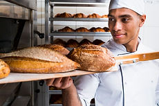 young-male-baker-taking-out-with-wooden-