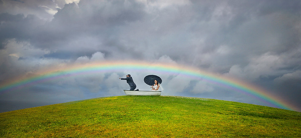 A quirky wedding photo with the wedding couple in a little rowboat on top of a grassy mound under a cloudy sky with a beautiful raibow arching above them. The wedding photo was taken in King Edward Park Newcastle.