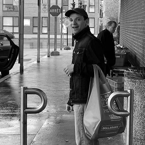Black and white image of an autistic man standing outside grocery store smiling while holding a bag of groceries.