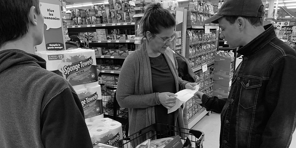 Black and white image of two men with ASD and a woman at a grocery store reading a grocery list.