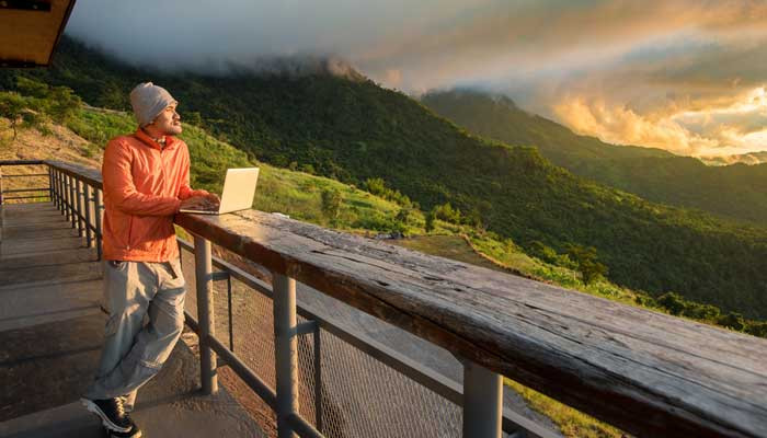 A man with laptop enjoying the magnificent view