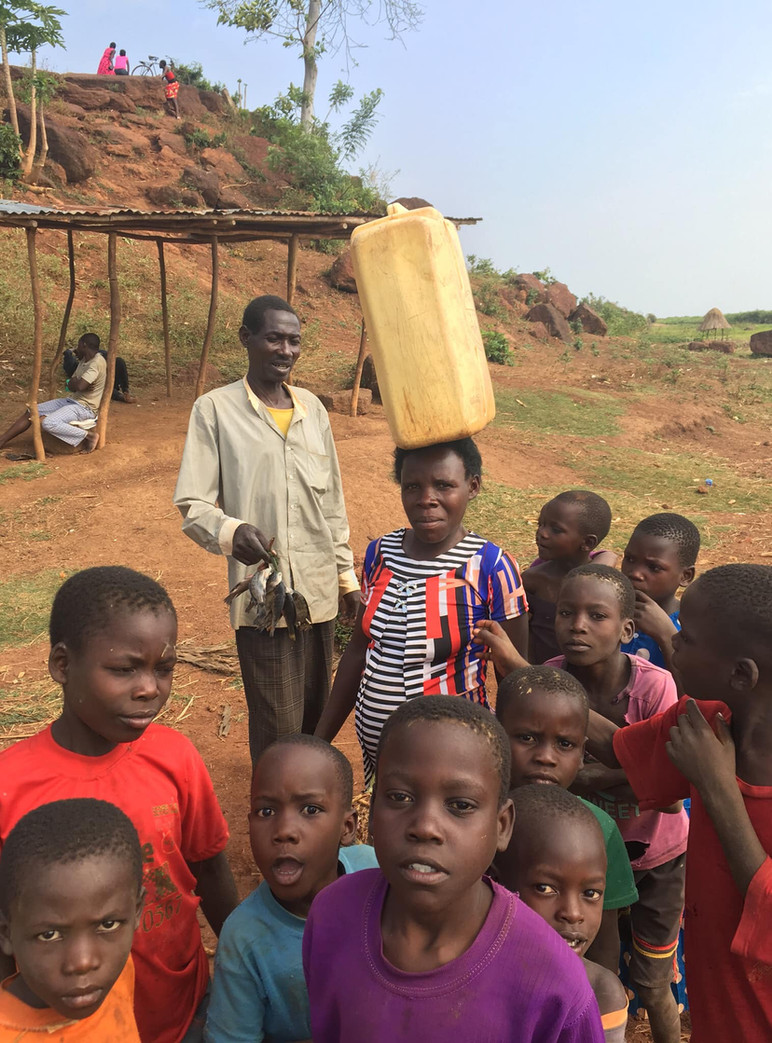 Ugandan Children with Woman Carrying Water to Village