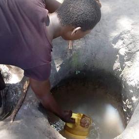 Young Woman Digging for Water in Uganda.
