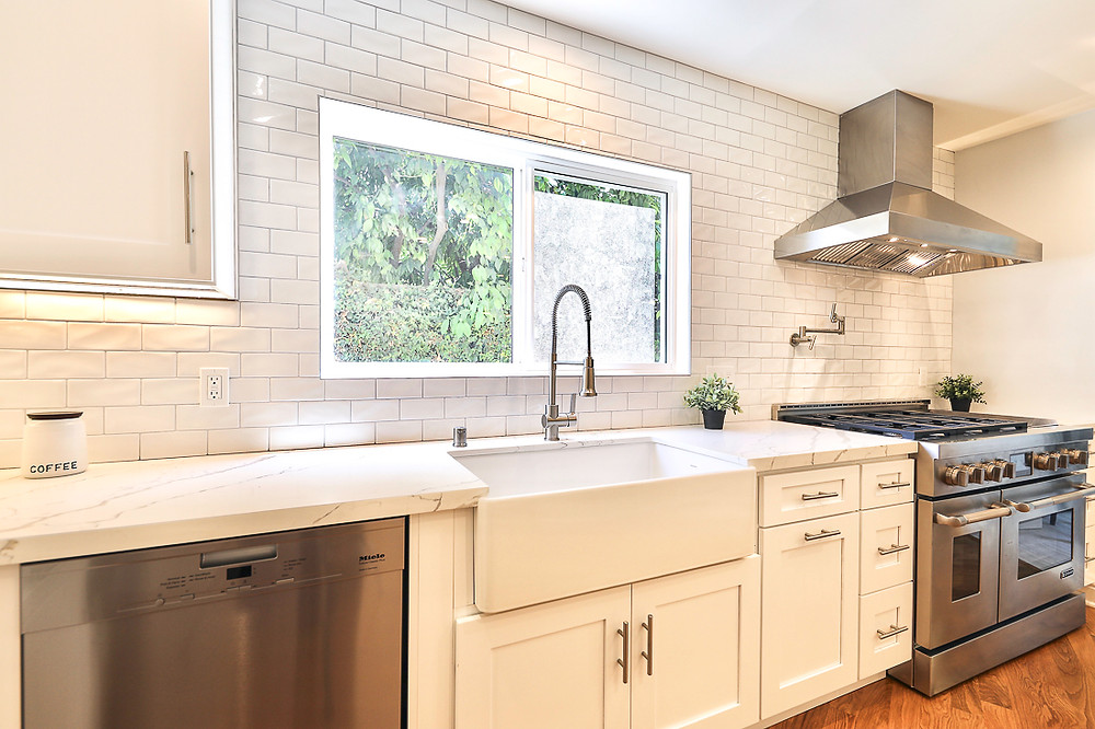 A white kitchen kitchen with farmhouse sink and counter to ceiling white subway tile