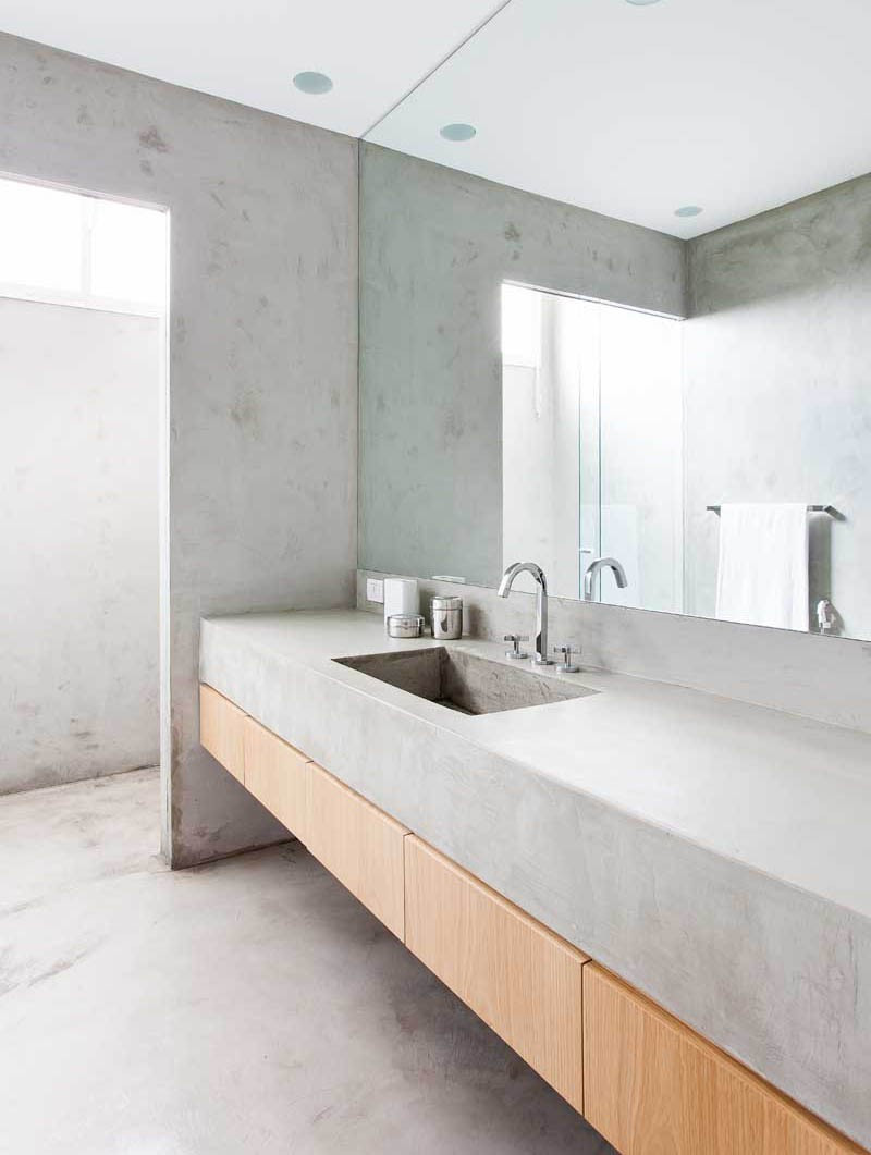 A bathroom with a concrete countertop and maple floating vanity plus concrete walls