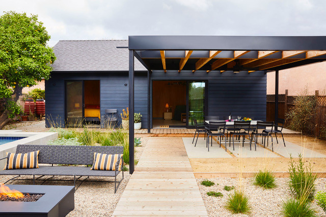 a modern blue and black accessory dwelling unit with hardscaping and outdoor seating