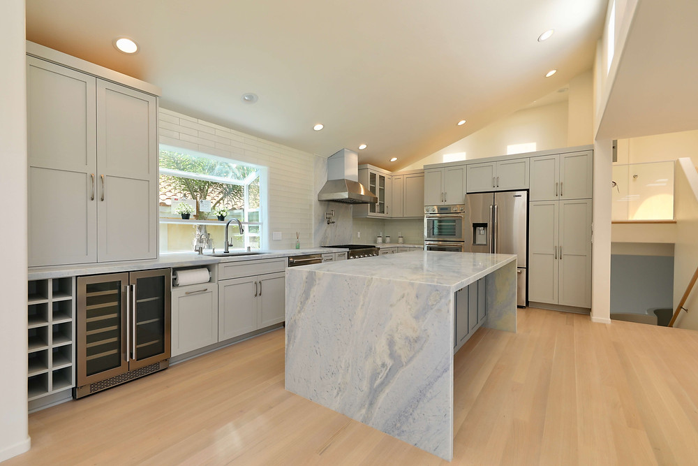 a waterfall edge countertop in a kitchen remodel with gray cabinets and white oak floors